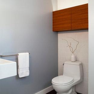 Idée de décoration pour un petit WC et toilettes tradition avec un placard à porte plane, des portes de placard en bois brun, un WC à poser, un carrelage blanc, des carreaux de céramique, un mur gris, un sol en carrelage de porcelaine, un lavabo suspendu et un sol gris.