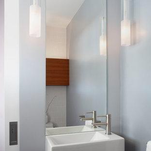 Cette photo montre un petit WC et toilettes chic avec un placard à porte plane, des portes de placard en bois brun, un WC à poser, un carrelage blanc, des carreaux de céramique, un mur gris, un sol en carrelage de porcelaine, un lavabo suspendu et un sol gris.