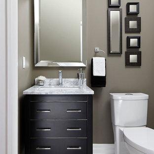 Bild på ett litet vintage vit vitt toalett, med en toalettstol med separat cisternkåpa, grå kakel, porslinskakel, grå väggar, klinkergolv i porslin, ett undermonterad handfat, marmorbänkskiva, luckor med profilerade fronter, svarta skåp och vitt golv
