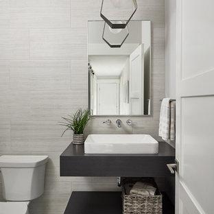 Aménagement d'un WC et toilettes classique avec un placard sans porte, des portes de placard en bois sombre, un carrelage gris, des carreaux de porcelaine, un mur gris, un sol en carrelage de porcelaine, un lavabo intégré, un plan de toilette en bois, un sol gris, un plan de toilette marron et meuble-lavabo suspendu.