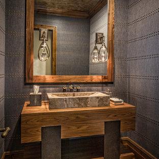 Cette image montre un WC et toilettes chalet de taille moyenne avec un placard sans porte, des portes de placard en bois brun, un mur gris, un sol en bois brun, un lavabo posé, un plan de toilette en bois, un sol marron et un plan de toilette marron.