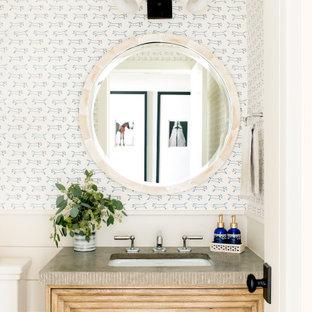 Cette photo montre un WC et toilettes nature avec un placard en trompe-l'oeil, des portes de placard en bois clair, un mur multicolore, un lavabo encastré, un plan de toilette gris et du papier peint.