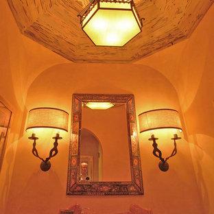 Inspiration för mellanstora medelhavsstil toaletter, med ett undermonterad handfat, orange väggar och granitbänkskiva