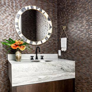 На фото: туалет в средиземноморском стиле с плоскими фасадами, темными деревянными фасадами, разноцветными стенами, светлым паркетным полом, врезной раковиной и разноцветной столешницей с