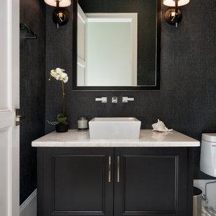Cette photo montre un WC et toilettes chic de taille moyenne avec un placard avec porte à panneau encastré, des portes de placard noires, un WC séparé, un mur noir, un sol en carrelage de céramique, une vasque, un plan de toilette en quartz modifié et un sol multicolore.