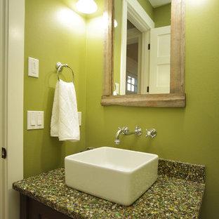 シアトルの小さいトラディショナルスタイルのおしゃれなトイレ・洗面所 (落し込みパネル扉のキャビネット、濃色木目調キャビネット、分離型トイレ、緑の壁、濃色無垢フローリング、ベッセル式洗面器、再生グラスカウンター、茶色い床、グリーンの洗面カウンター) の写真
