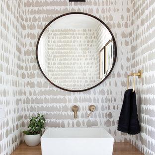Aménagement d'un WC et toilettes contemporain de taille moyenne avec un mur multicolore, un lavabo posé, un plan de toilette en bois et un plan de toilette marron.