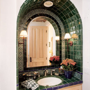 Design ideas for a mid-sized mediterranean powder room in San Diego with light wood cabinets, tile benchtops, a two-piece toilet, an undermount sink, recessed-panel cabinets, green tile and ceramic tile.