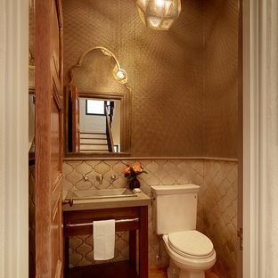 Small mediterranean cloakroom in San Francisco with dark wood cabinets, a two-piece toilet, beige tiles, ceramic tiles, medium hardwood flooring, limestone worktops, freestanding cabinets, brown walls, a console sink and brown floors.
