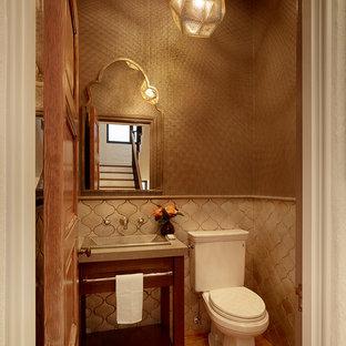 Kleine Mediterrane Gästetoilette mit dunklen Holzschränken, Wandtoilette mit Spülkasten, beigefarbenen Fliesen, Keramikfliesen, braunem Holzboden, Kalkstein-Waschbecken/Waschtisch, verzierten Schränken, brauner Wandfarbe, Waschtischkonsole und braunem Boden in San Francisco