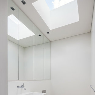 Modern powder room in Sydney with a wall-mount toilet, white walls, a wall-mount sink and white floor.