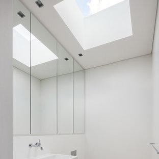 Ispirazione per un bagno di servizio moderno con WC sospeso, pareti bianche, lavabo sospeso e pavimento bianco