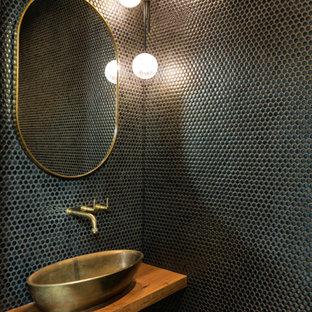 Bild på ett industriellt toalett, med mosaik och träbänkskiva
