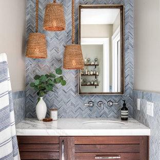 Idées déco pour un WC et toilettes classique avec un placard à porte shaker, des portes de placard en bois sombre, un mur beige, un lavabo encastré et un plan de toilette blanc.