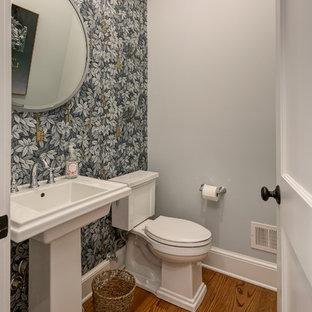 Cette image montre un petit WC et toilettes traditionnel avec un WC séparé, un sol en bois brun, un lavabo de ferme, un mur multicolore et un sol marron.