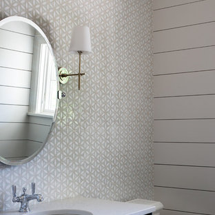 Small nautical cloakroom in Kansas City with beaded cabinets, blue cabinets, a two-piece toilet, multi-coloured tiles, mosaic tiles, white walls, a submerged sink, engineered stone worktops and white worktops.