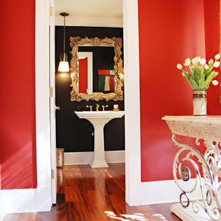 Idée de décoration pour un petit WC et toilettes tradition avec un WC à poser, un mur noir, un sol en bois brun, un lavabo de ferme et un sol multicolore.