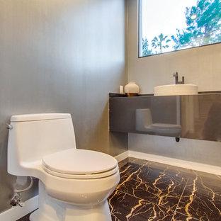 ロサンゼルスの小さいコンテンポラリースタイルのおしゃれなトイレ・洗面所 (一体型トイレ、グレーの壁、磁器タイルの床、ベッセル式洗面器、亜鉛の洗面台、グレーの床) の写真