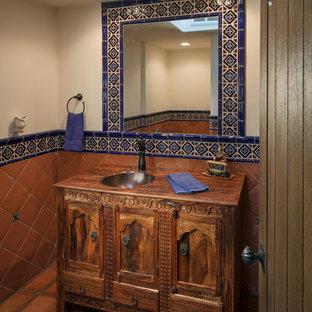 Kleine Mediterrane Gästetoilette mit verzierten Schränken, Waschtisch aus Holz, blauen Fliesen, orangefarbenen Fliesen, Terrakottaboden, Terrakottafliesen, beiger Wandfarbe, Einbauwaschbecken, dunklen Holzschränken und brauner Waschtischplatte in Phoenix