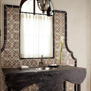 На фото: туалет среднего размера в средиземноморском стиле с накладной раковиной, бежевыми стенами, керамической плиткой, столешницей из дерева и черной столешницей с