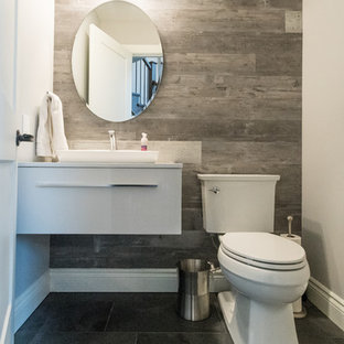 This is an example of a small classic cloakroom in Toronto with flat-panel cabinets, white cabinets, a two-piece toilet, grey tiles, grey walls, engineered stone worktops, grey floors, white worktops, porcelain tiles, slate flooring and a vessel sink.