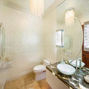На фото: туалет среднего размера в морском стиле с плоскими фасадами, белыми фасадами, унитазом-моноблоком, белой плиткой, стеклянной плиткой, белыми стенами, полом из травертина, настольной раковиной, столешницей из оникса и бежевым полом с