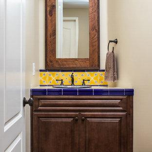 Exemple d'un petit WC et toilettes sud-ouest américain avec un placard avec porte à panneau surélevé, des portes de placard marrons, un WC séparé, des carreaux de céramique, un mur beige, un sol en bois foncé, un lavabo posé, un plan de toilette en carrelage, un sol marron et un plan de toilette bleu.