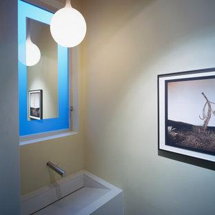 Пример оригинального дизайна: туалет в стиле модернизм с фасадами цвета дерева среднего тона, инсталляцией, желтой плиткой, желтыми стенами, полом из терраццо, раковиной с несколькими смесителями, столешницей из бетона, белым полом и серой столешницей