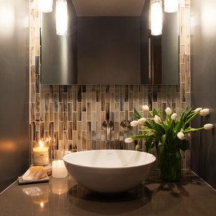 На фото: маленький туалет в стиле современная классика с настольной раковиной, столешницей из искусственного кварца, разноцветной плиткой и стеклянной плиткой с