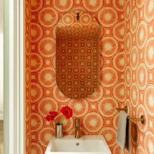 Aménagement d'un petit WC et toilettes contemporain avec un mur orange et un lavabo suspendu.