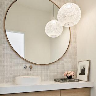 Mittelgroße Moderne Gästetoilette mit flächenbündigen Schrankfronten, hellen Holzschränken, Porzellan-Bodenfliesen, Aufsatzwaschbecken, Quarzwerkstein-Waschtisch, weißer Waschtischplatte, grauer Wandfarbe und grauem Boden in Dallas