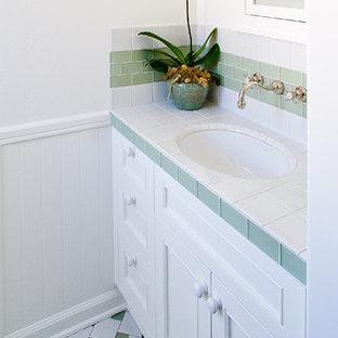 Неиссякаемый источник вдохновения для домашнего уюта: маленький туалет в классическом стиле с врезной раковиной, белыми фасадами, столешницей из плитки, белой плиткой, зеленой плиткой, стеклянной плиткой, белыми стенами, полом из керамогранита и фасадами с утопленной филенкой