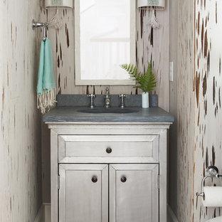 На фото: маленький туалет в стиле современная классика с фасадами островного типа, серыми фасадами, паркетным полом среднего тона, монолитной раковиной, бежевыми стенами, бежевым полом и серой столешницей с