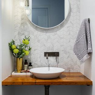На фото: туалет в современном стиле с керамогранитной плиткой, полом из керамогранита, столешницей из дерева, серым полом, серой плиткой, белой плиткой, белыми стенами, настольной раковиной, коричневой столешницей и фасадами цвета дерева среднего тона с