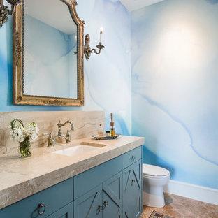 Idee per un bagno di servizio chic di medie dimensioni con ante con riquadro incassato, ante blu, piastrelle blu, piastrelle in ceramica, pareti bianche, pavimento in terracotta, lavabo sottopiano, top in marmo, pavimento rosso e top beige