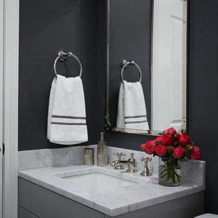 Idee per un piccolo bagno di servizio chic con ante grigie, pareti nere, lavabo sottopiano, top in marmo, ante con riquadro incassato e top bianco