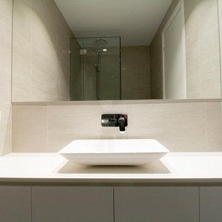На фото: маленький туалет в современном стиле с фасадами с филенкой типа жалюзи, белыми фасадами, унитазом-моноблоком, бежевой плиткой, керамической плиткой, полом из керамической плитки, настольной раковиной, столешницей из бетона, серым полом и белой столешницей с
