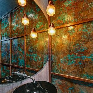 На фото: огромный туалет с разноцветными стенами, подвесной раковиной и напольной тумбой с