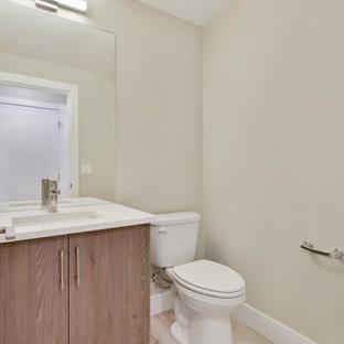 Cette photo montre un petit WC et toilettes moderne avec un placard à porte plane, des portes de placard en bois brun, un WC à poser, un mur beige, sol en stratifié, un lavabo encastré, un plan de toilette en surface solide, un sol gris, un plan de toilette blanc et meuble-lavabo encastré.