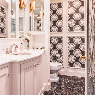 ボストンの広いトラディショナルスタイルのおしゃれなトイレ・洗面所 (インセット扉のキャビネット、白いキャビネット、一体型トイレ、白い壁、大理石の床、アンダーカウンター洗面器、大理石の洗面台、黒い床、白い洗面カウンター、造り付け洗面台、格子天井、壁紙) の写真