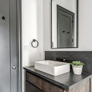 На фото: туалеты в современном стиле с плоскими фасадами, темными деревянными фасадами, раздельным унитазом, белыми стенами, полом из керамической плитки, настольной раковиной, столешницей из бетона, разноцветным полом и серой столешницей
