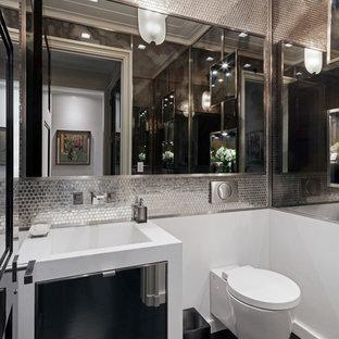 Inspiration pour un WC et toilettes design avec des carreaux de miroir, un sol en bois foncé et un lavabo intégré.