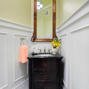 Cette photo montre un petit WC et toilettes chic avec un placard avec porte à panneau encastré, des portes de placard en bois sombre, un WC séparé, un mur jaune, un sol en marbre, un lavabo encastré, un plan de toilette en surface solide, un sol blanc et un plan de toilette noir.