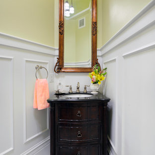 Inspiration for a small traditional cloakroom in St Louis with recessed-panel cabinets, dark wood cabinets, a two-piece toilet, yellow walls, marble flooring, a submerged sink, solid surface worktops, white floors and black worktops.