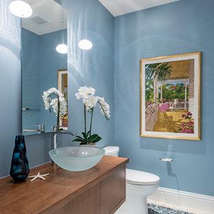 Идея дизайна: туалет в морском стиле с плоскими фасадами, фасадами цвета дерева среднего тона, синими стенами, полом из мозаичной плитки, настольной раковиной, столешницей из дерева, синим полом и коричневой столешницей