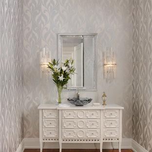 Foto på ett vintage vit toalett, med luckor med profilerade fronter, vita skåp, flerfärgade väggar, mellanmörkt trägolv, ett fristående handfat, träbänkskiva och brunt golv