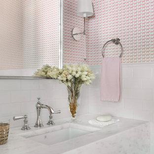 Inspiration pour un WC et toilettes traditionnel de taille moyenne avec un carrelage blanc, un carrelage métro, un mur rose, un lavabo encastré, un plan de toilette en marbre et un plan de toilette blanc.