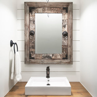 Example of a mountain style powder room design in Other with a vessel sink, wood countertops, white walls and brown countertops