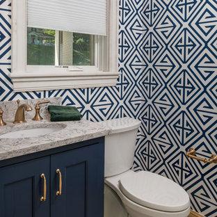 Inredning av ett maritimt litet grå grått toalett, med luckor med infälld panel, blå skåp, en toalettstol med separat cisternkåpa, flerfärgade väggar, klinkergolv i porslin, ett undermonterad handfat, grått golv och granitbänkskiva