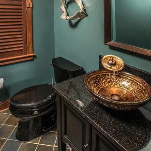 На фото: маленький туалет в стиле фьюжн с фасадами с выступающей филенкой, черными фасадами, раздельным унитазом, синими стенами, полом из керамогранита, настольной раковиной, столешницей из гранита и разноцветным полом с